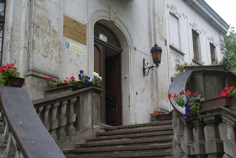 Schody prowadzące do budynku, Na ścianie lampa z epoki, szyldy. Na balustradzie ustawione skrzynki z czerwonymi kwiatami.